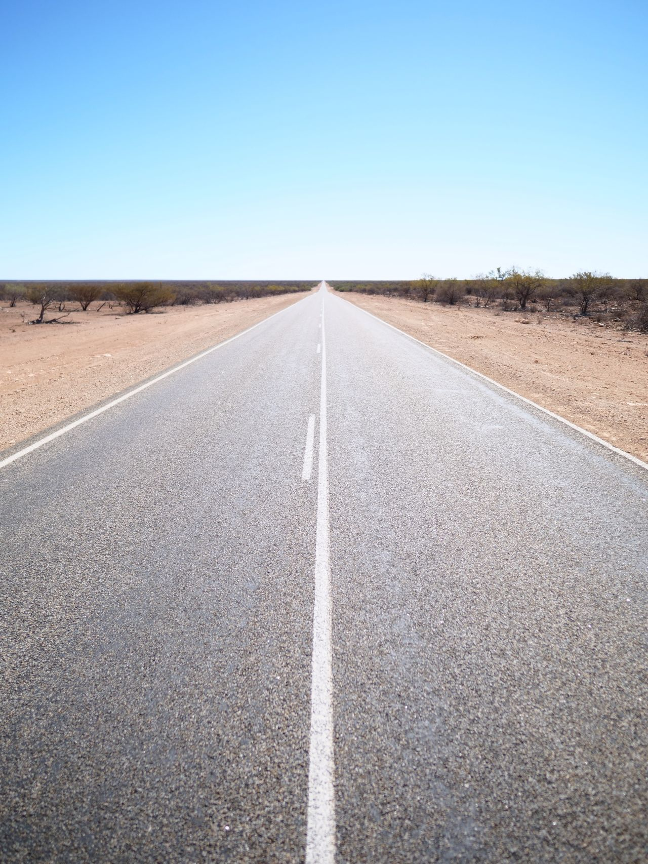Empty road passing through landscape against clear sky