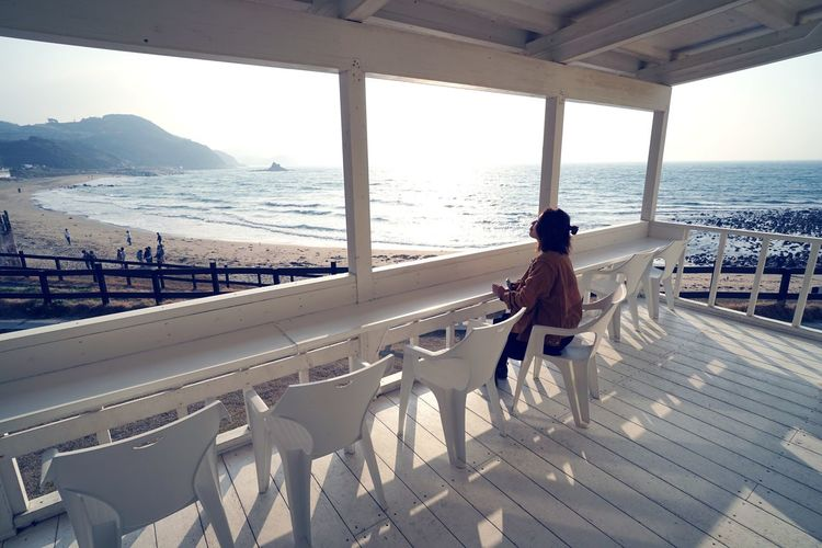 Side view of woman sitting on chair at observation point by sea