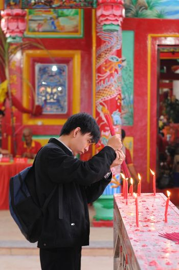 Side View Of Man Igniting Incense Stick At Temple