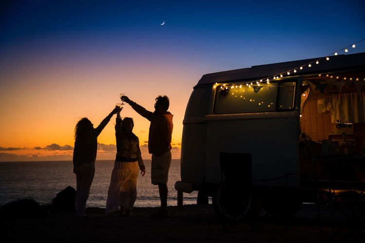 Friends toasting wineglasses while standing by camper van at beach against sky during sunset