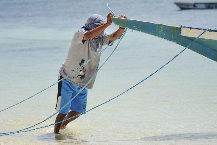 Fisherman Pushing Boat At Sea Shore