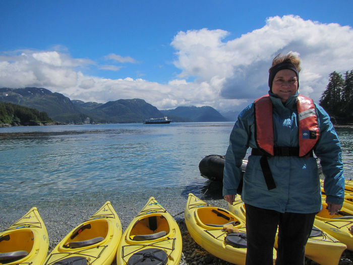 Exploring Alaska's Coastal Wilderness. Kayaking at George Island. Love Yourself Adventure Alaska Beauty In Nature Casual Clothing Cloud - Sky Day George Island Kayaks Leisure Activity Lifestyles Looking At Camera Mountain Mountain Range Nature One Person Outdoors Real People Sky Standing Water