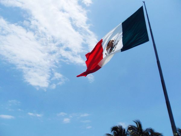 Mexican Flag View from my Car . Patriotism Low Angle View Sky Red Cloud - Sky Day Wind Pride Outdoors No People Blue Eagle Green Color White Red Cancun