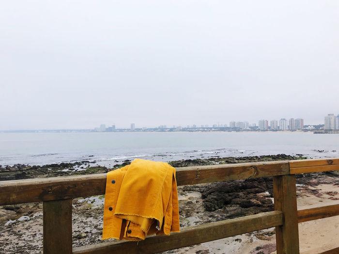 Jacket on railing at beach against clear sky