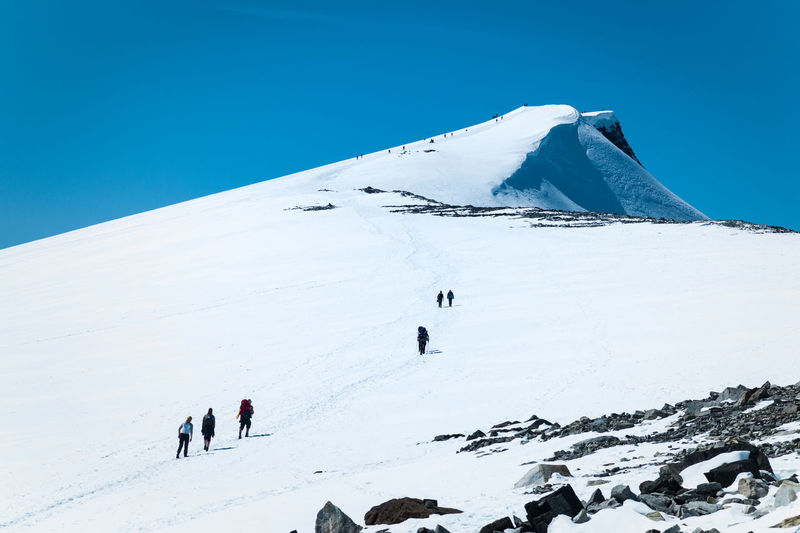 People On Snowcapped Mountains Against Clear Blue Sky