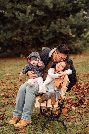 High angle view of father with daughter against autumn leaves