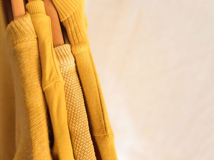 Yellow illuminated color winter sweaters on wooden hangers. trendy fashion autumn warm clothes
