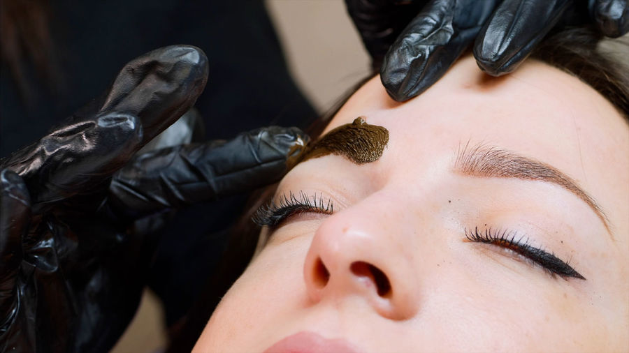 Cropped hands of beautician coloring woman eyebrow