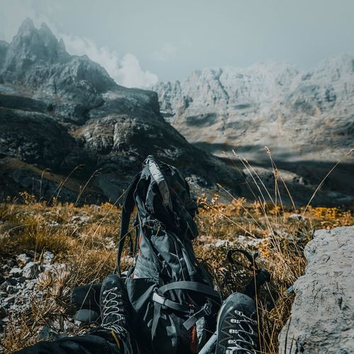 Low Section Of Person With Backpack On Mountains During Winter