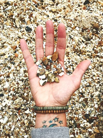 Directly above shot of person holding pebbles