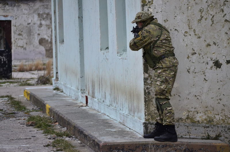 Army soldier aiming rifle while standing behind house in city
