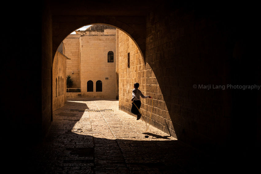 Jumping rope playing in Jerusalem. Arch Architecture Boy Building Composition Day Horizontal Israel Jerusalem Jumping Jumping Rope Leisure Activity Lifestyles Light And Shadow Marji Lang Photography Motion One Person Play Playing Street Photography Streetphotography Sunny Tunnel Walkway The Street Photographer - 2016 EyeEm Awards