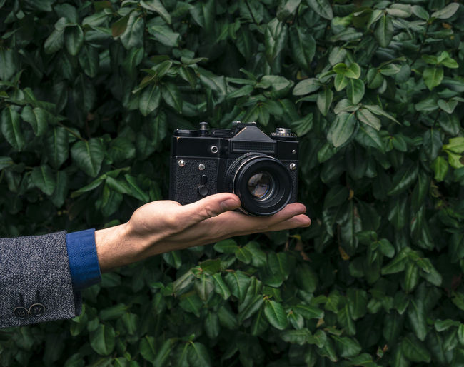 Male hand holding a vintage film camera in the air. Green nature in the background. Camera Camera - Photographic Equipment Film Green Looking At Camera Retro Analog Black Day Holding Human Body Part Human Hand Leaves Lens Old One Person Outdoor Outdoors Plant Vintage Zenit