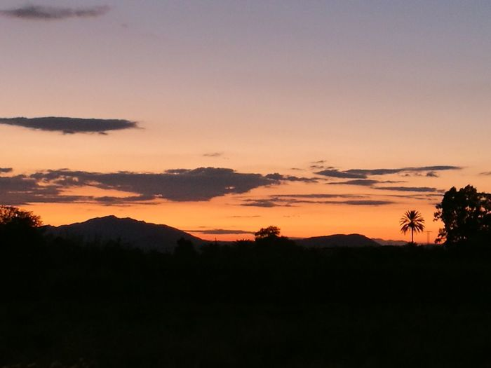 Scenic view of silhouette mountains against sky during sunrise