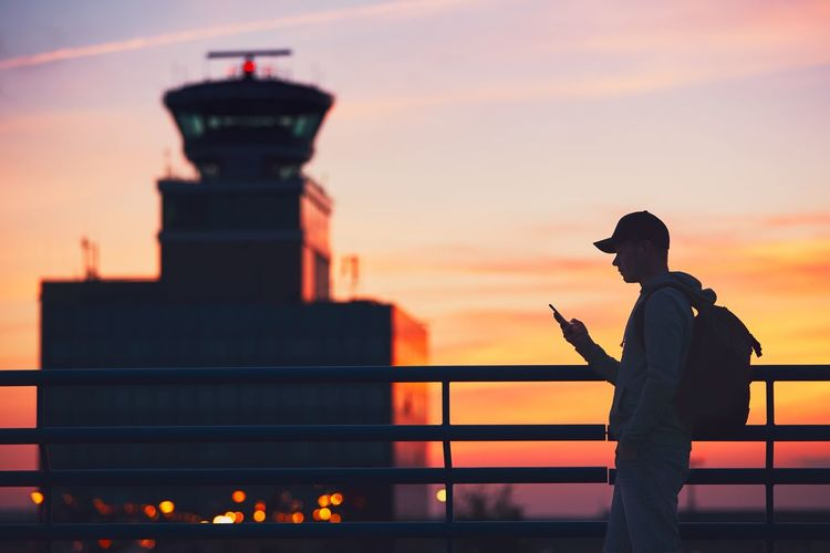 Silhouette of the traveler with mobile phone at the airport. Air Traffic Control Tower at the amazing sunset. Airport Airportphotography Communication Connection Flying Journey Lifestyles Loneliness Lonely Man Mobile Phone People Real People Silhouette Smart Phone Summer Sunset Telecommunications Equipment Travel Traveler Traveling Trip Using Phone Vacations Wireless Technology