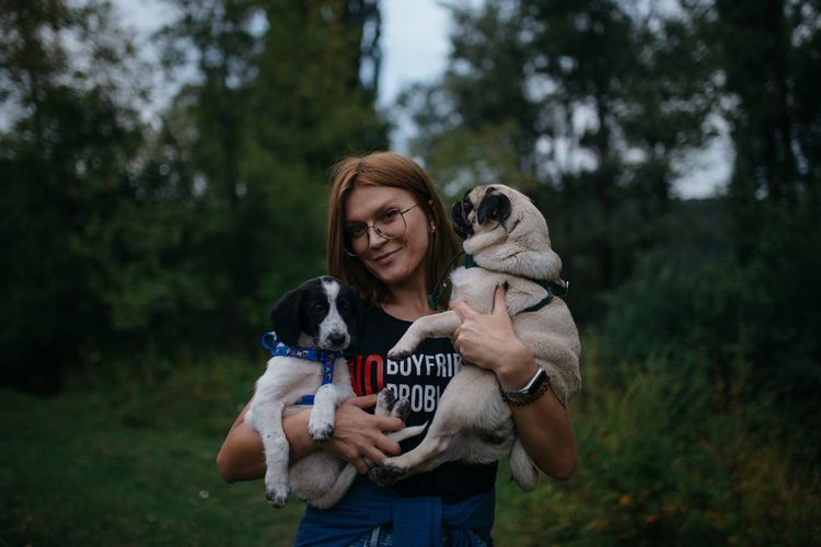 Portrait of smiling woman holding dog standing against trees