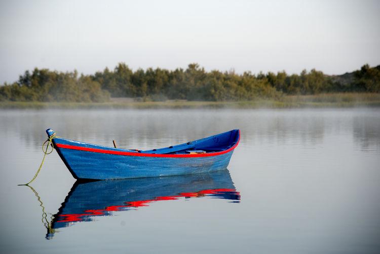 Fishing boat in lake against sky
