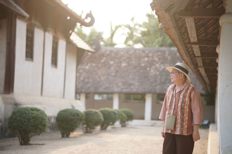 Woman standing by house