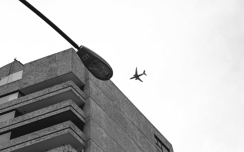 Low angle view of airplane flying above building