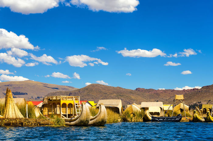 View of the Uros Floating Islands floating on Lake Titicaca in Peru Architecture Beach Boat Colorful Decor Ethnic Floating Houses Inca Isla Island Islands Lake Landscape Manmade Peru Puno Puno, Perú Scene Titicaca Titicaca Lake Totora Tourism Uros Uros Island