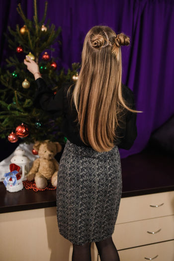 Rear view of girl standing at home