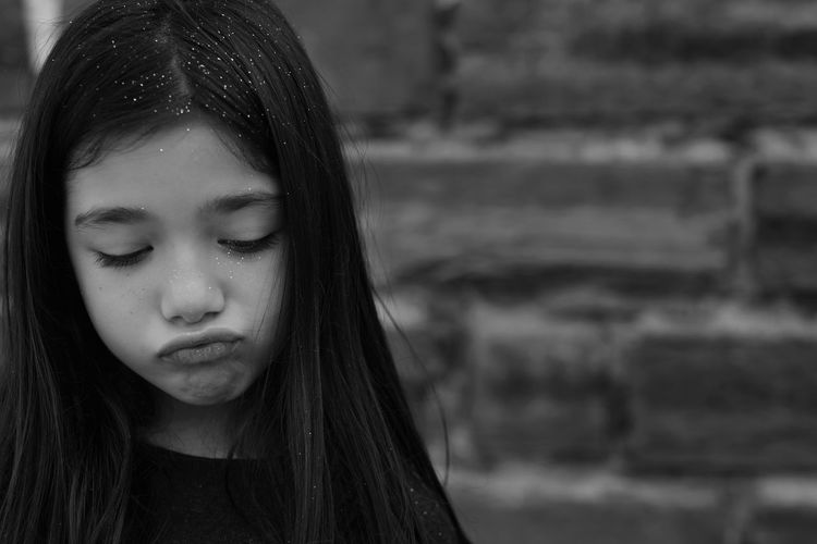 Close-Up Of Sad Girl Against Brick Wall