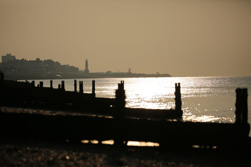 The sun threaded itself through the tide and appeared to turn salt to metal. Architecture Beauty In Nature Building Exterior Built Structure City Cityscape Clear Sky Day HerneBay Nature No People Outdoors Scenics Sea Silhouette Sky Sunset Water