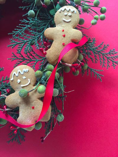 Gingerbread men on wreath with copy space Berries Christmas Wreath Close-up Cookies Copy Space Decorated Gingerbread Men Green Greenery Holiday Desserts Natural Light Nobody Overhead Phone Camera Red Red Background Ribbon Studio Shot Vertical