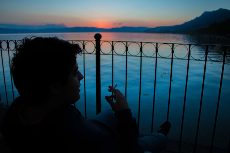 jUST sMOKING oNE Blue Color Mexico Beauty In Nature Day Leisure Activity Lifestyles Lowkey  Nature One Person Orange Color Outdoors People Phtography Real People Sea Silhouette Sky Sunset Water Waterfront The Portraitist - 2018 EyeEm Awards