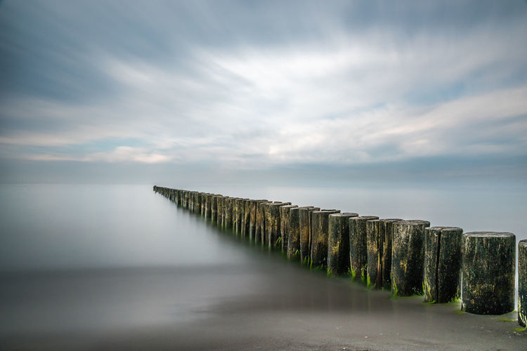 Row of wooden posts in sea against cloudy sky during foggy weather
