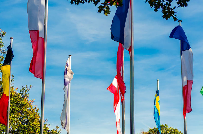 VARIOUS NATIONAL FLAGS ON POLES OUTDOORS
