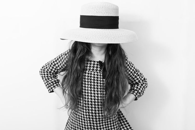 Low section of woman wearing hat standing against white background