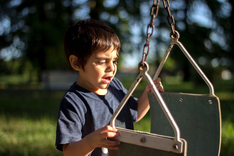 Cute boy looking at swing while standing on playground