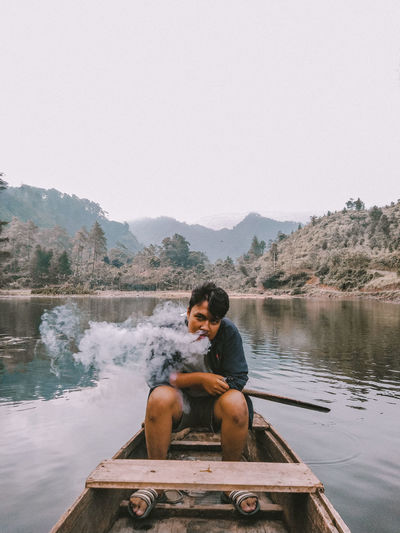 Man smoking while sitting in boat on lake against clear sky