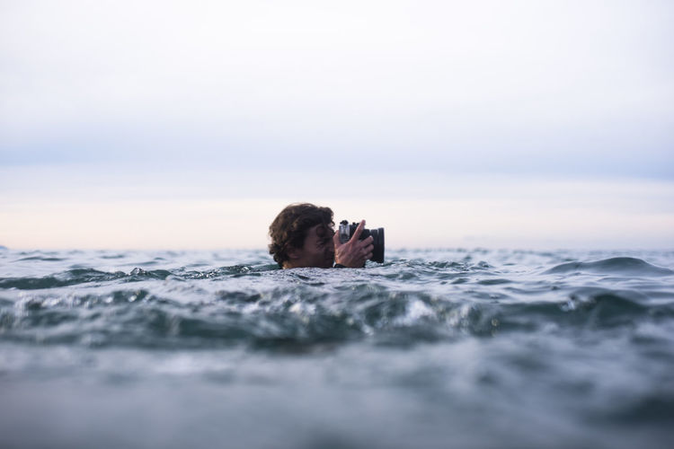 Portrait of man swimming in sea against sky