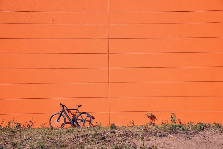 Bicycle parked on land against orange wall