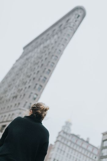 Rear view of woman standing near flatiron building