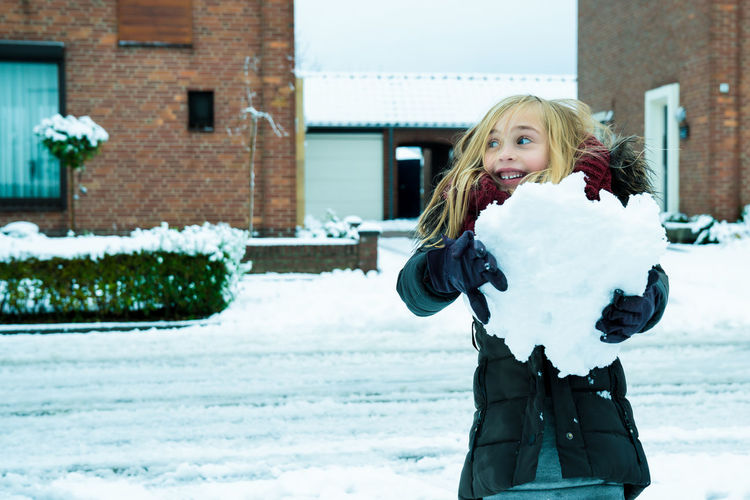 Portrait of a child having fun in the snow, holding a big snowball Having Fun Beautiful Woman Blond Hair Child Childhood Cold Temperature Day Girl Happiness House Leisure Activity Lifestyles One Person Outdoors Playing Portrait Real People Smiling Snow Warm Clothing Winter Young Women Exploring Fun Snowing Snowfall Winter Coat Blizzard Deep Snow Frozen Weather Condition