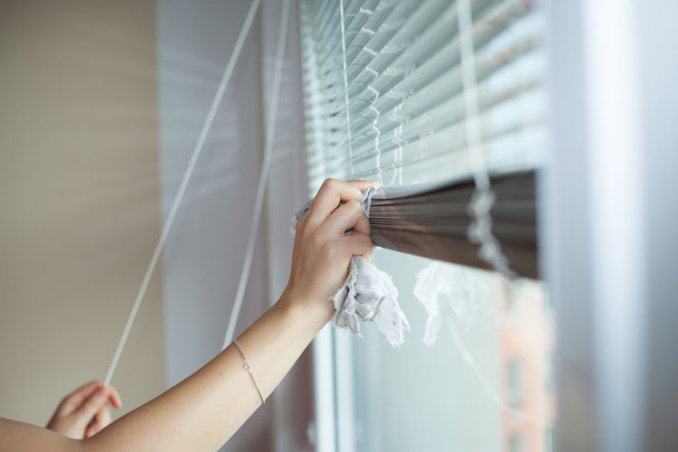 Midsection of person holding hands hanging on window