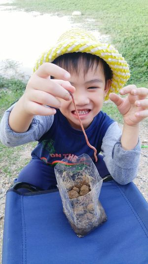 Close-up of smiling boy playing with earthworm on field