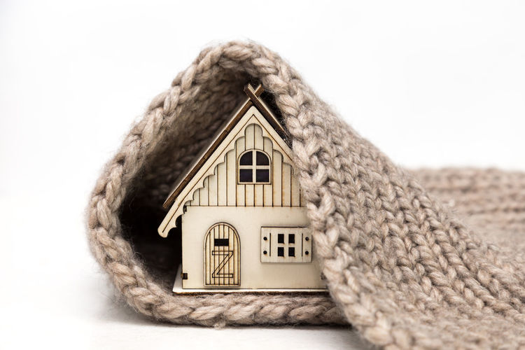 Close-up of model home and doormat against white background