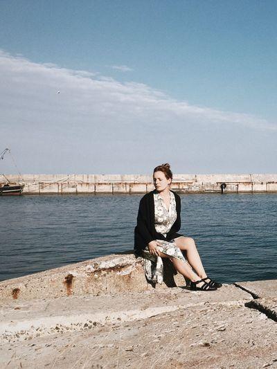 Full length of woman sitting at promenade against sky