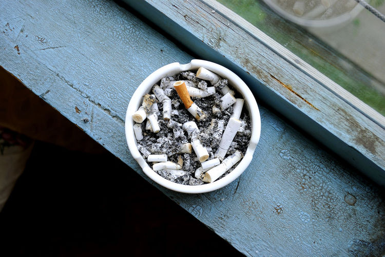 High angle view of ashtray on window sill