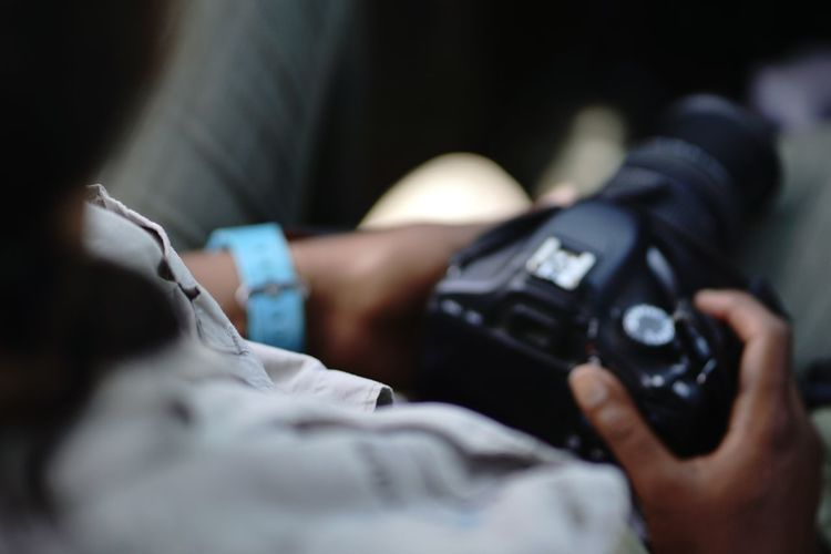 Close-up of hand holding camera on safari with blue watch