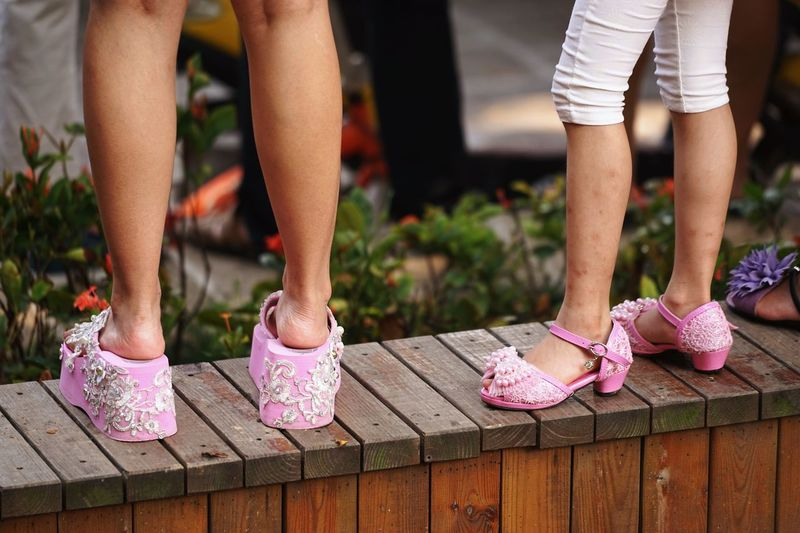 Low section of girls with pink footwear standing on wooden wall