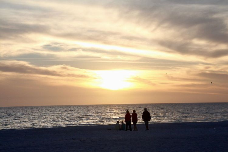 Silhouette people on beach against cloudy sky during sunset