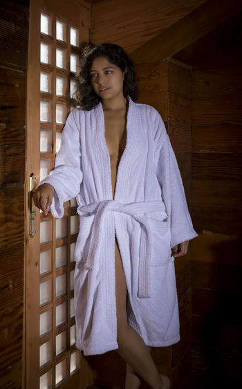 Young woman wearing white bathrobe by door
