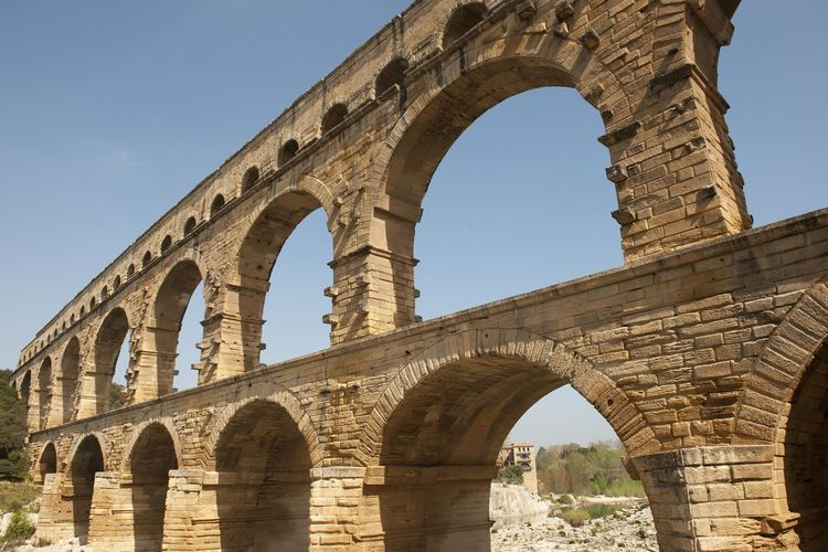 Low angle view of aqueduct against clear blue sky