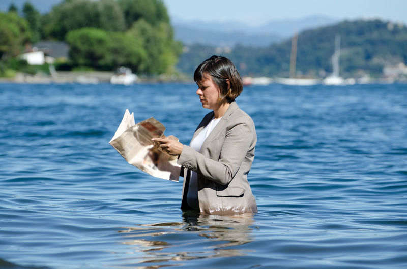 Side View Of Woman Reading Newspaper While Standing In Lake