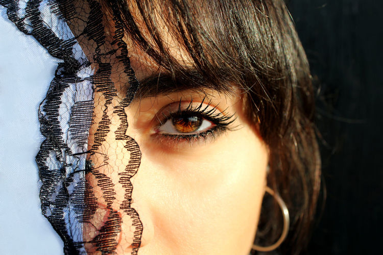 Close-Up Portrait Of Woman Wearing Mascara By Textile In Sunny Day